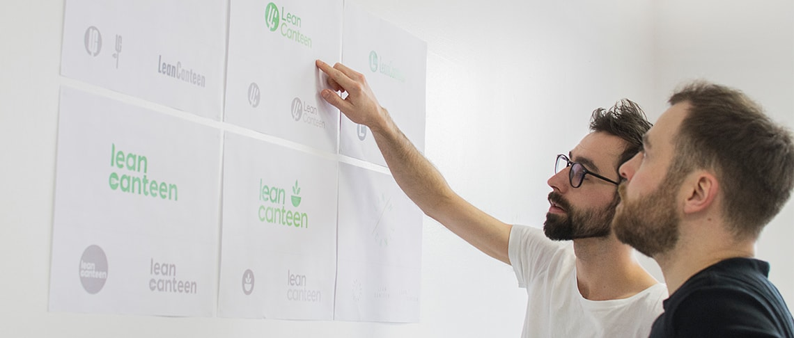 Two graphic designers reviewing logo design and brand identity concepts