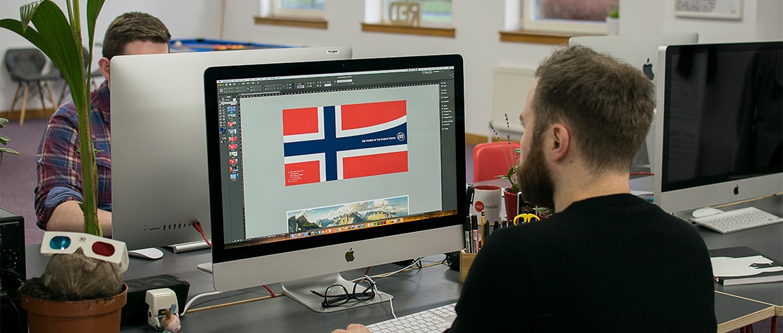 Strive Digital graphic designer working at a computer designing a corporate brochure for ISS Norway