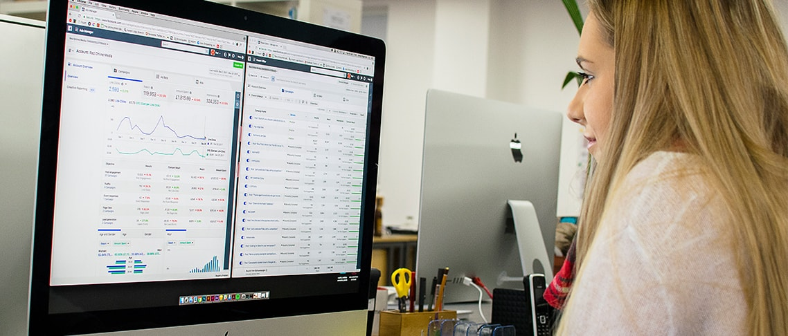 Strive Digital social media marketing assistant working at a computer and reviewing Facebook analytics.