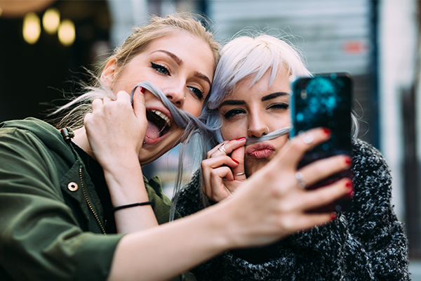 Strive Digital: Marketing Millenials via Snapchat blog post cover, with a red and purple gradient background and Strive Digital logo, and a faded image of two girls taking a selfie